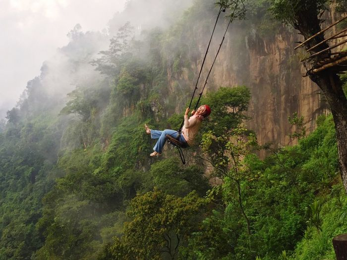 Woman swinging against mountain