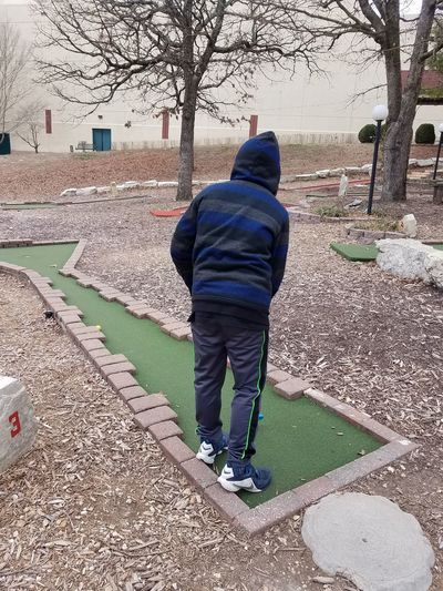 Child Boy Leaves Bare Tree Miniature Golfing Putt Putt Golf Club Playing Golf Taking A Swing Kid Playing Real People One Person Full Length Rear View Building Exterior Winter Day Built Structure Leisure Activity Architecture Standing Nature Warm Clothing Clothing Outdoors Casual Clothing Hood - Clothing