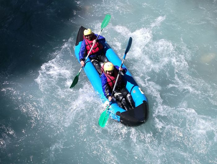 High angle view of friends rafting in river