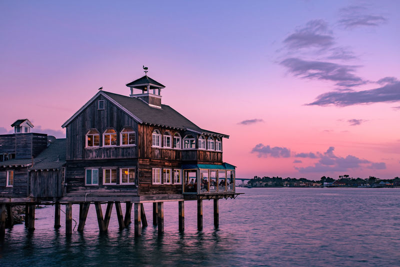 Building by sea against sky during sunset
