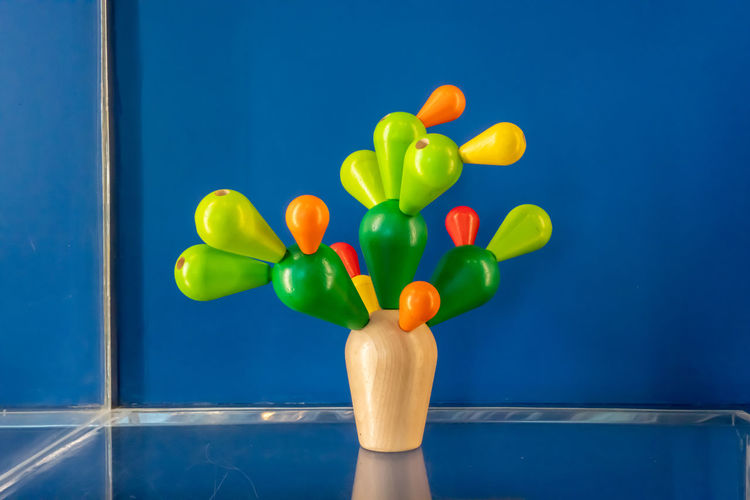 Close-up of multi colored balloons against blue wall