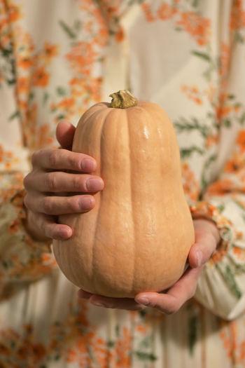 Close-up of hand holding pumpkin