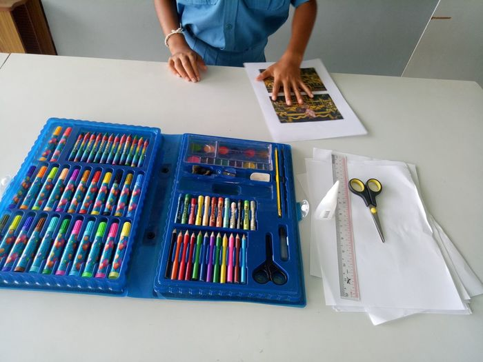High angle view of child with art and craft equipment on table