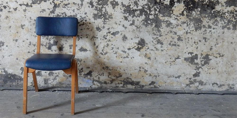 Abandoned chair on table against wall