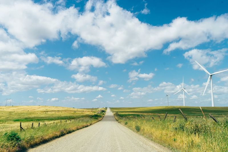 The Way Forward Wind Turbine Wind Power Environmental Conservation Alternative Energy Road Field Sky Diminishing Perspective Nature Landscape Day Fuel And Power Generation Renewable Energy Outdoors No People Cloud - Sky Grass Rural Scene Windmill