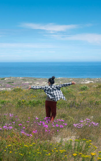Rear view of woman standing by plants against sea and sky