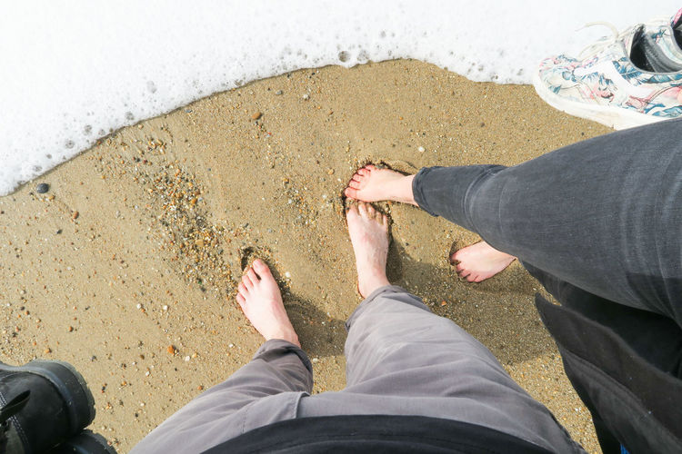 high angle view on barefoot feet of a couple standing on the beach of porto, portugal POV barefoot Feet Sand White Water Couple Low Section Beach Standing Human Leg Sand Togetherness Shoe High Angle View Personal Perspective