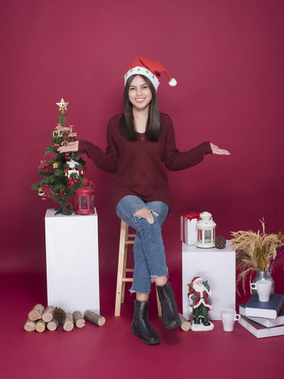 Young woman with christmas gifts sitting against red background