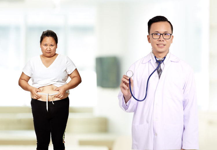 Portrait of male doctor with overweight female patient in hospital