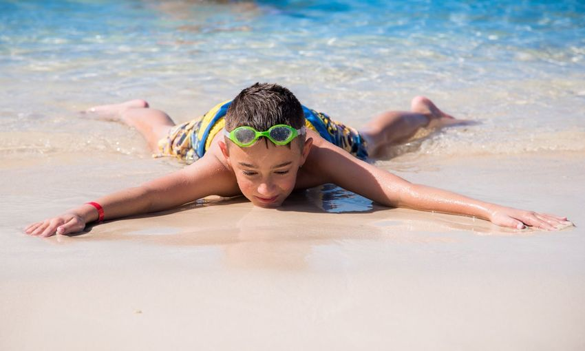 Close-up of boy lying on beach