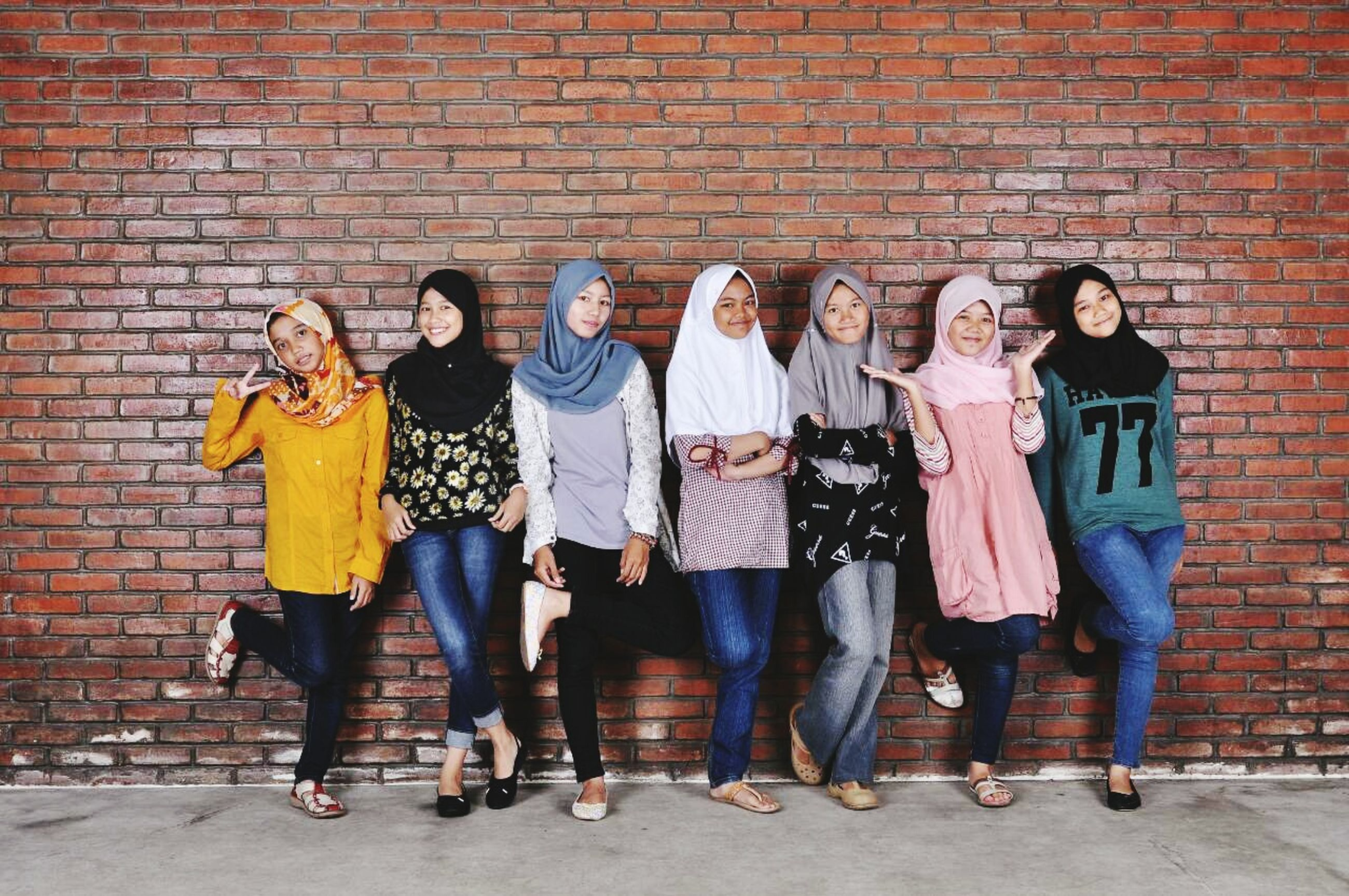 lifestyles, togetherness, casual clothing, full length, leisure activity, men, love, wall - building feature, bonding, built structure, standing, person, architecture, front view, friendship, building exterior, traditional clothing, brick wall