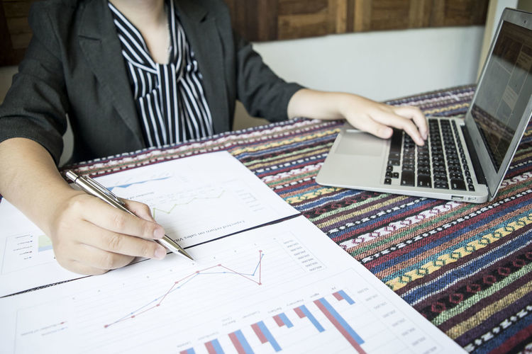 Businesswoman using laptop while working over graphs and charts at desk in office