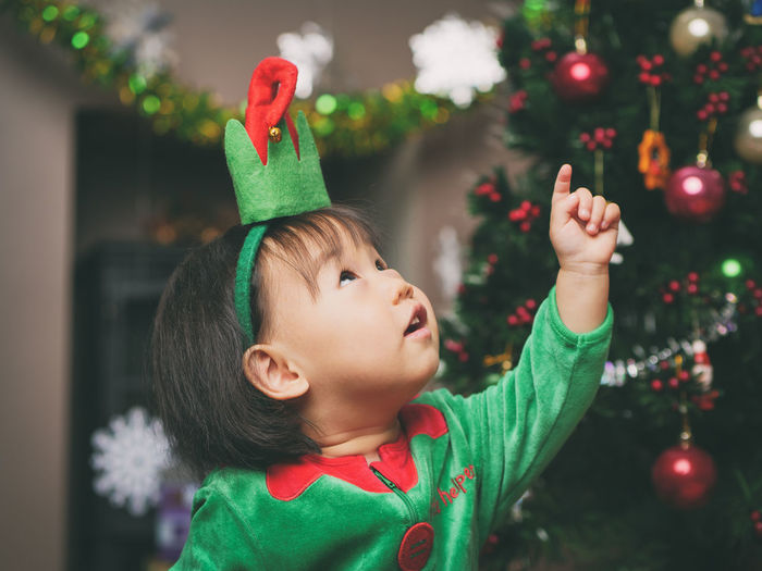 Elf Asian Baby Girl Celebration Childhood Christmas Christmas Decoration Christmas Ornament Christmas Tree Close-up Cute Day Focus On Foreground Green Color Headshot Indoors  Innocence Lifestyles One Person Real People Tree