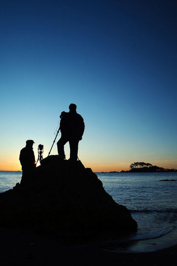 Silhouette man standing on shore against clear sky during sunset