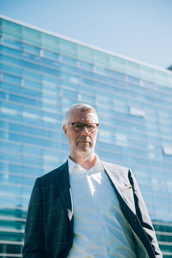 Low angle portrait of senior businessman standing against modern building