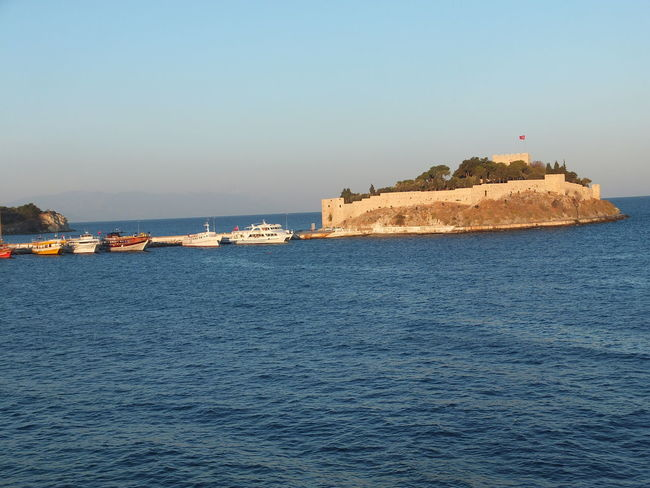 Sunrise over Pidgeon Island Beauty In Nature Blue Sky Boats Composition Flag Fort Horizon Over Water Idyllic Kusadasi Nature No People Outdoor Photography Pidgeon Island Rippled Rock Formation Scenics Sea Sunlight Sunrise Tourist Attraction  Tranquil Scene Tranquility Turkey Water Waterfront