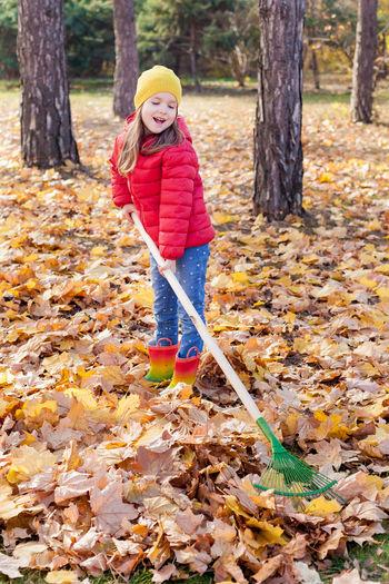 Girl raking leaves during autumn