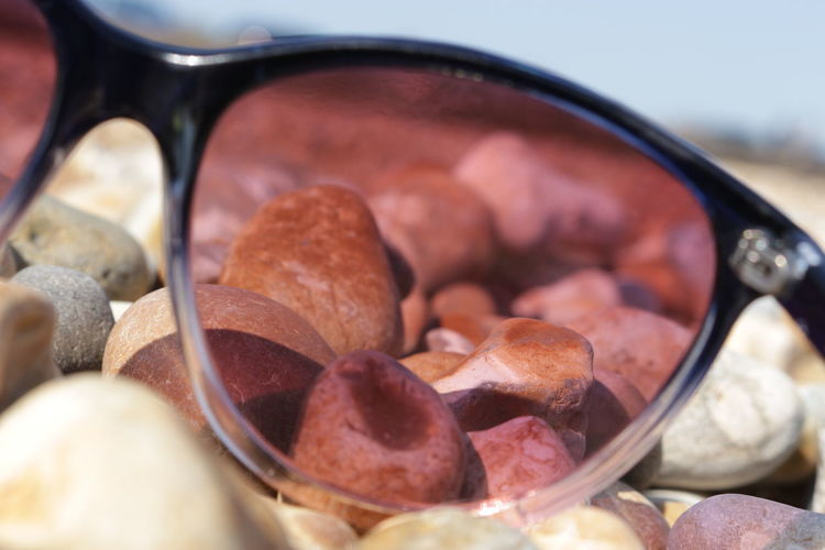 Close-Up Of Sunglasses On Pebbles