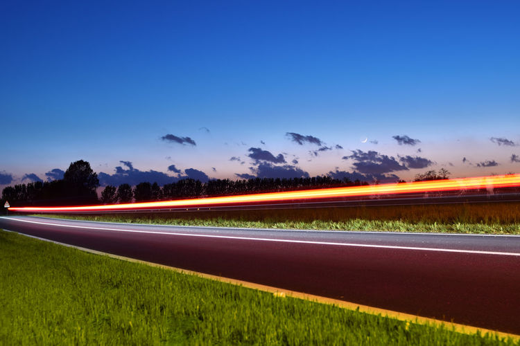 Light trails on road amidst field against blue sky