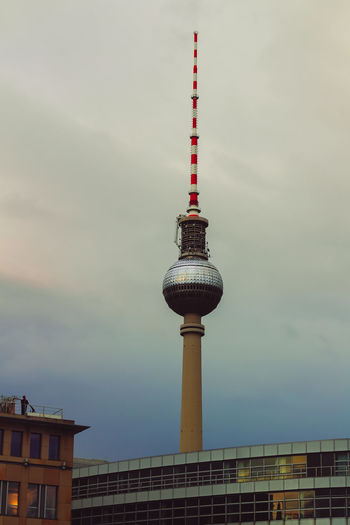 Communications tower in city against sky