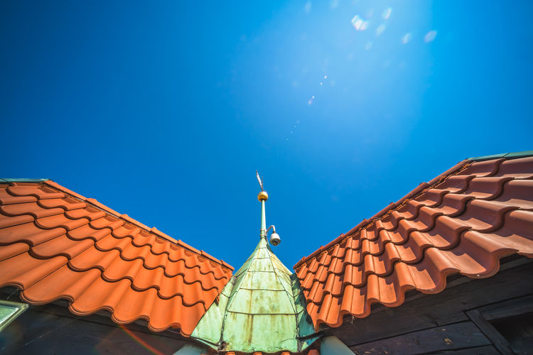 Low angle view of building roof against clear blue sky