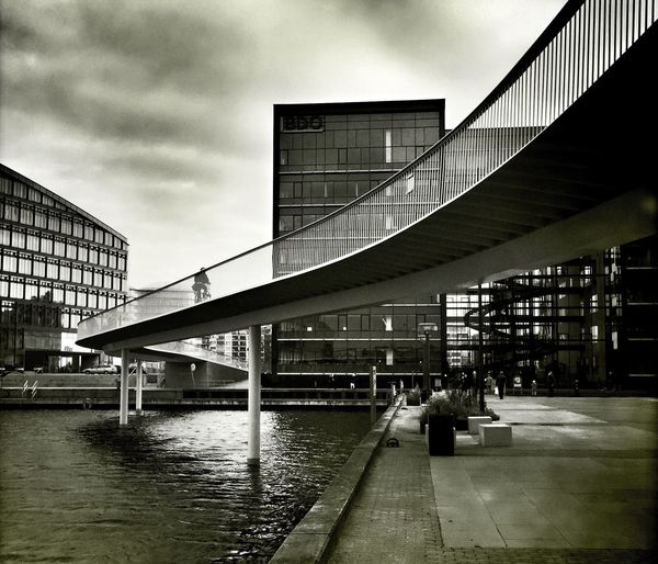 Elevated Walkway Curving Above City Square And Pond