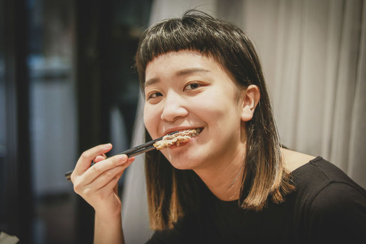 Portrait of woman eating food at home