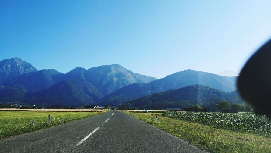 Road leading towards mountains against clear sky