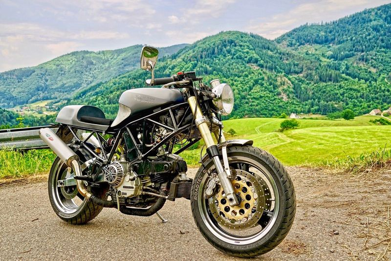 Café Racer Motorcycle Ducati Nature Mountain Transportation Mode Of Transport Land Vehicle Mountain Range Beauty In Nature Green Color Day Travel Adventure Scenics Outdoors Sport Landscape Tree Grass Sky One Person
