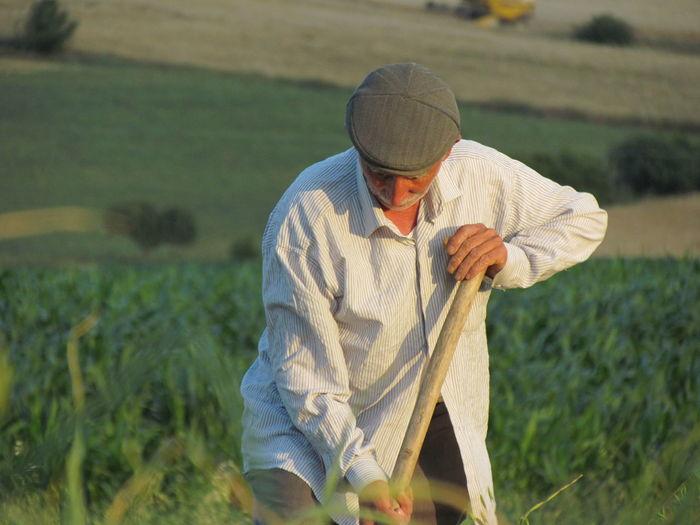 Man gardening by tool on field