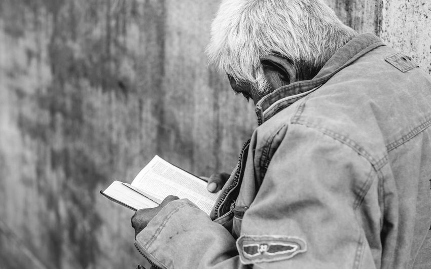 Close-up of senior man reading book against wall