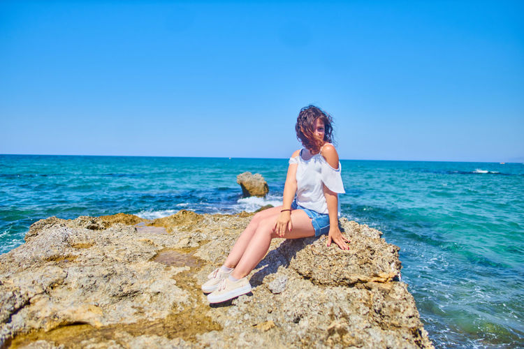 Young Woman Sitting On Rock At Beach Against Clear Blue Sky
