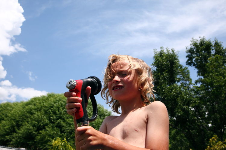 Low angle view of boy holding garden hose