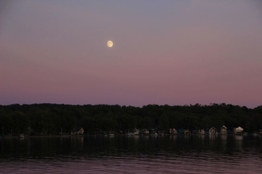 moon rises in the beautiful sunset reflection over Conesus Lake, one of New York's Finger Lakes Finger Lakes Of Western New York Water Reflections Astronomy Beauty In Nature Moon Moonrise Nature Night No People Outdoors Scenics Sky Sunset Tranquility Tree Upstate New York Water