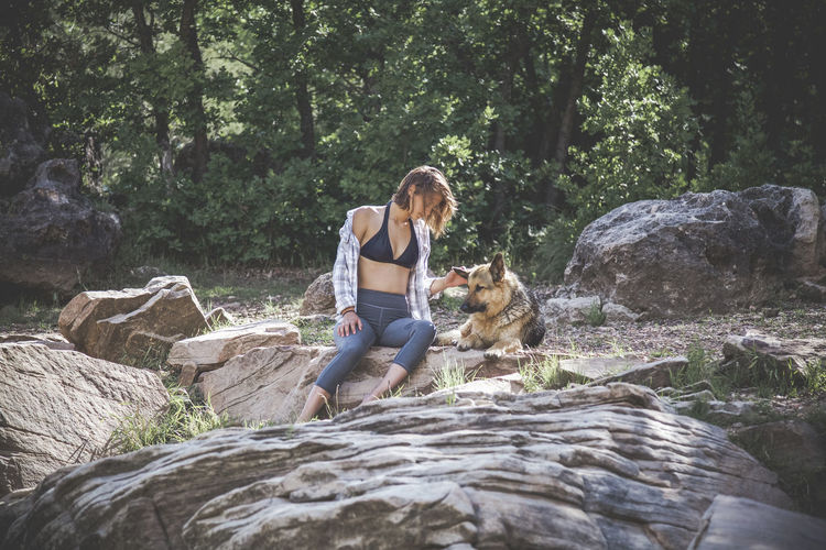 Young Woman With Dog Sitting On Rock Against Trees