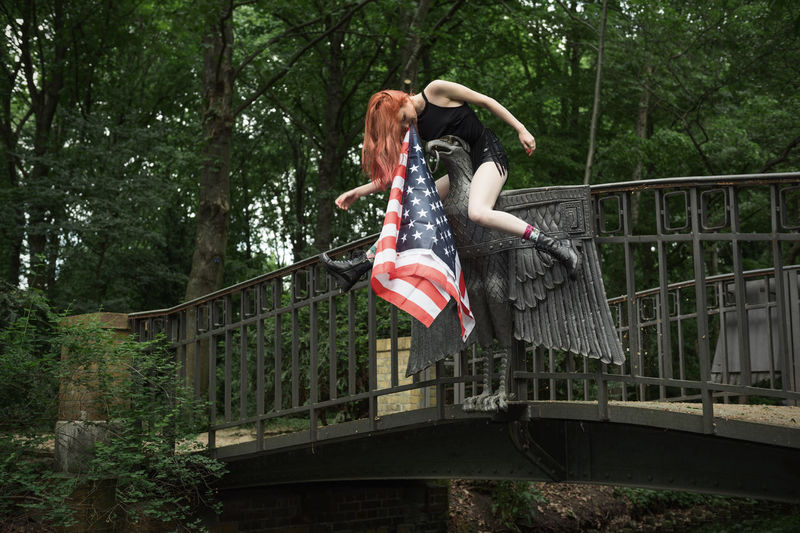 Woman Carrying American Flag In Mouth While Sitting On Statue Against Trees