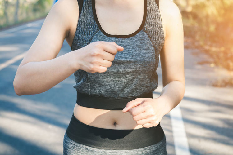 Midsection of woman jogging on road