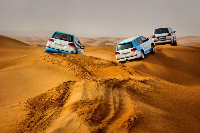 Cars On Sand Dune In Desert