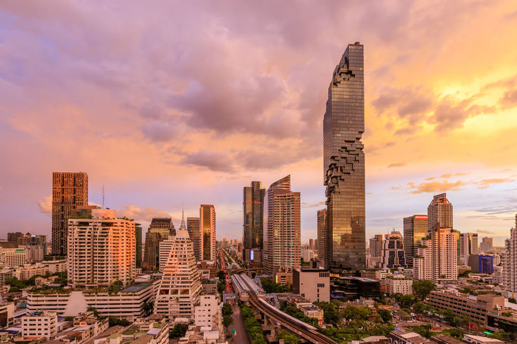 Modern buildings in city against sky during sunset