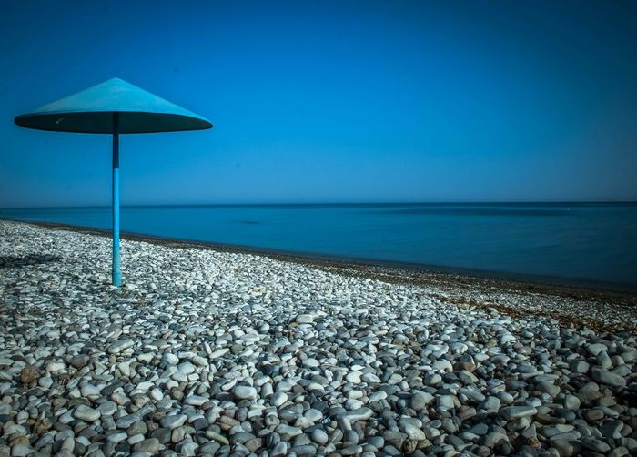 Blue parasol on stones by sea against clear sky