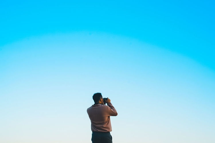 Rear view of man photographing against blue sky