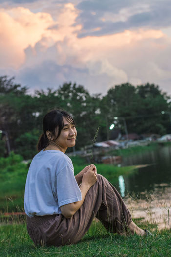 See the sunset Sky Beautiful Water Reflection. See The Sunset One Person Real People Plant Grass Sky Nature Leisure Activity Field Land Lifestyles Sitting Casual Clothing Cloud - Sky Women Adult Side View Young Adult Focus On Foreground Day Outdoors Contemplation Hairstyle