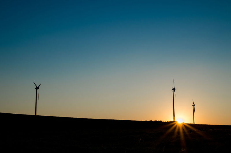 Silhouette of windmill on field against sky at sunset