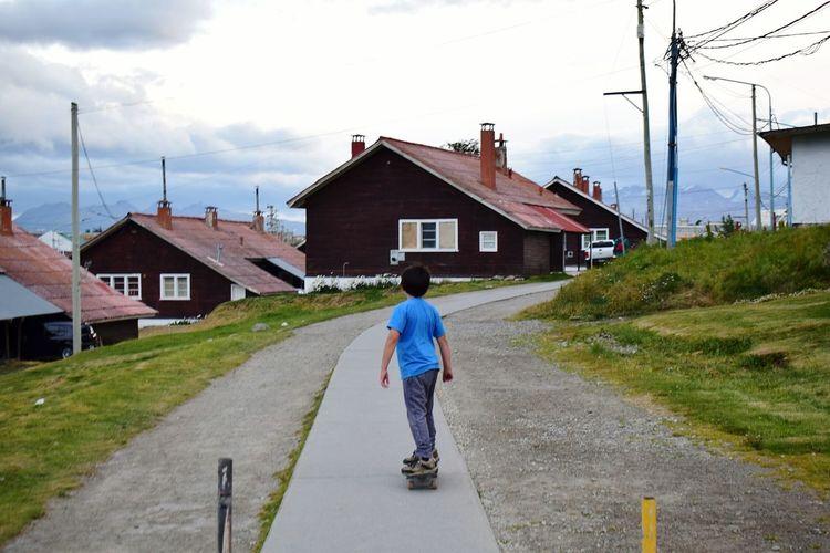 Boy skateboarding on road against houses