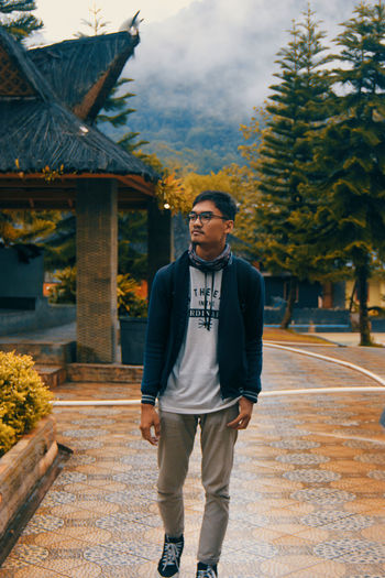 Young man looking away while standing on street at park