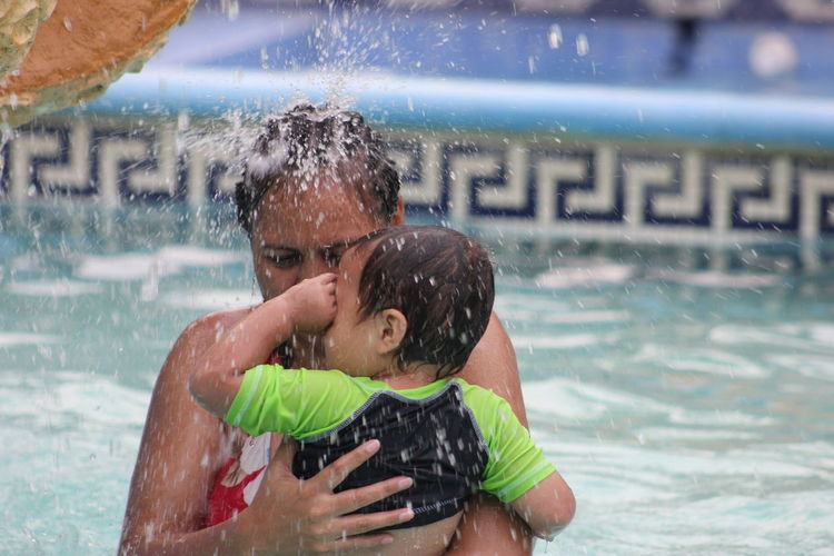 Mother and son swimming in pool