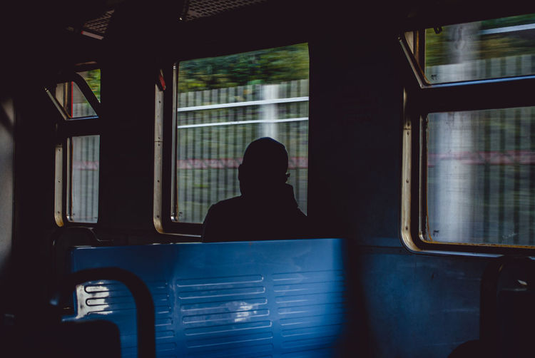 Silhouette of man sitting in train