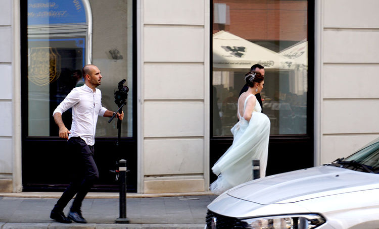 newlyweds followed by a photographer Following Funny Groom Wedding Bride Faster Follow Hurry Motion Newlywed Photographer Street Street Photography Streetphotography Wedding Dress
