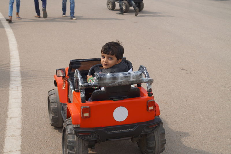 High angle view of boy driving toy car on street