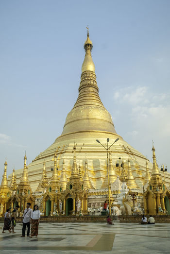 Yangon, Myanmar - February 22 2016 - the Shwedagon Pagoda, national icon of Myanmar in the afternoon Building Exterior Built Structure Architecture Religion Belief Place Of Worship Spirituality Sky Building Travel Destinations Yangon Myanmar National Icon Gold Gold Colored Blue Sunset Afternoon Tourism Day History Buddha Buddhism Religious  Spirituality Cityscape City Group Of People Men Cultures
